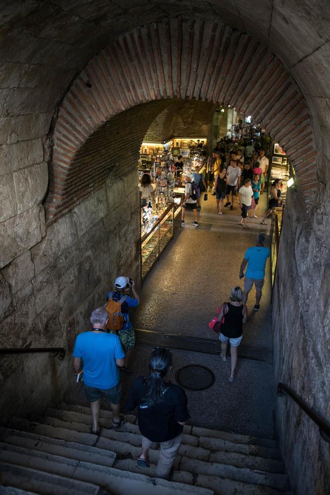 Ha a Peristiliumon tovább haladunk és lemegyünk a kapualjba, akkor egy hatalmas, boltíves terembe jutunk, tele képeslap- és szuvenírárusokkal