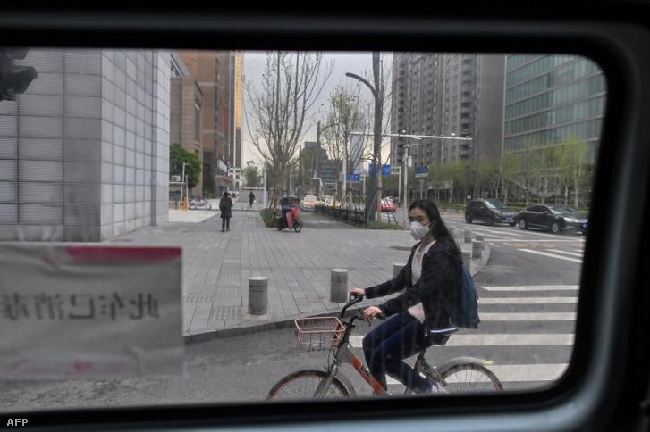 Arcmaszkot viselő lány biciklizik a kínai Hupej tartomány központjában, Vuhanban 2020 március 28-án, amikor a két hónapos szigorú vesztegzár után már enyhítettek a közlekedési korlátozásokon a városban.