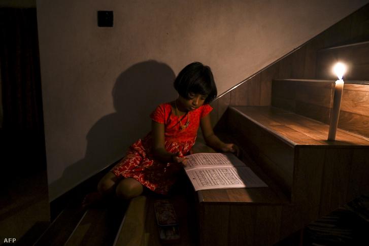 Egy lány könyvet olvas gyertyafény mellett az áramszünet alatt Colombo külvárosában, Biyagamaban, 2020. augusztus 18-án.