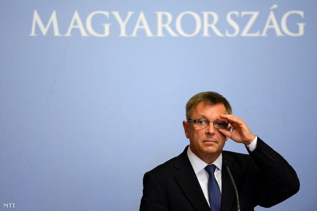 Matolcsy György igazítja szemüvegét, mielőtt sajtótájékoztatót tart a sajtótájékoztatót tart a Miniszterelnökségen