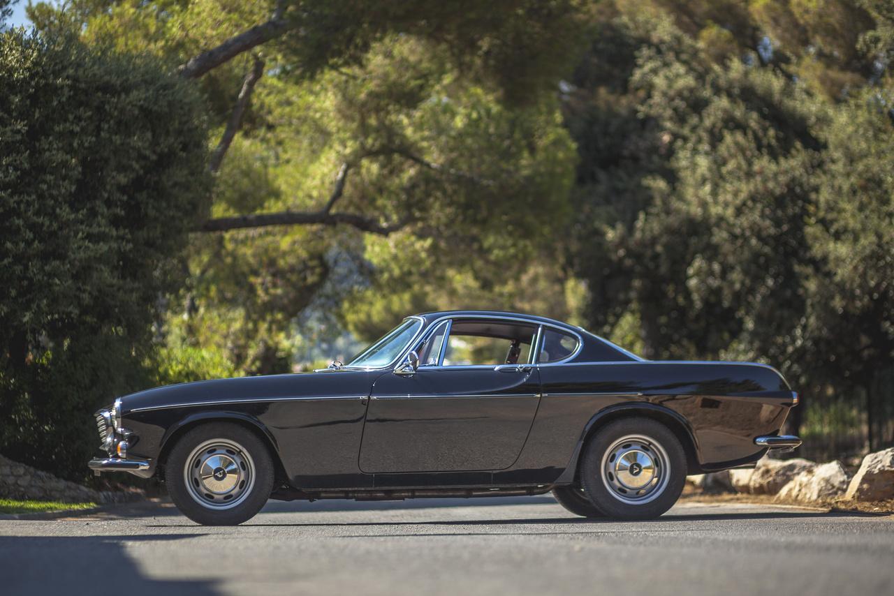 Andrea Volvója 1970-es, még karburátoros P1800S. Elég ritka belőle a fekete, és a dél-francia napsütésben gyönyörűen fest. Pelle Petterson formatervébe eszembe nem jutna belekötni, annyira tökéletesen találta el az arányokat. Az orrában van egy kis Ferrari 250 GT Boano, a fecskefarokban egy kis Amerika, a sziluettjében pedig az olasz tavak ékszere, a Riva hajója. Andrea nagy rajongója a Szentnek, mindig is vágyott egy P1800-ra, és három évvel ezelőtt meg is valósította az álmát.