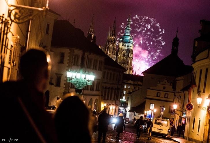 Az újévi tűzijáték fénye világítja meg az égboltot a prágai vár felett