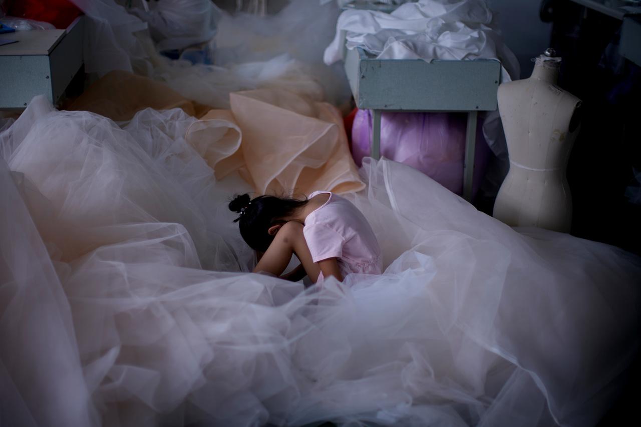 Egy kislány éppen a mobiltelefonján játszik egy szucsoui varroda padlóján felhalmozott anyagokon.