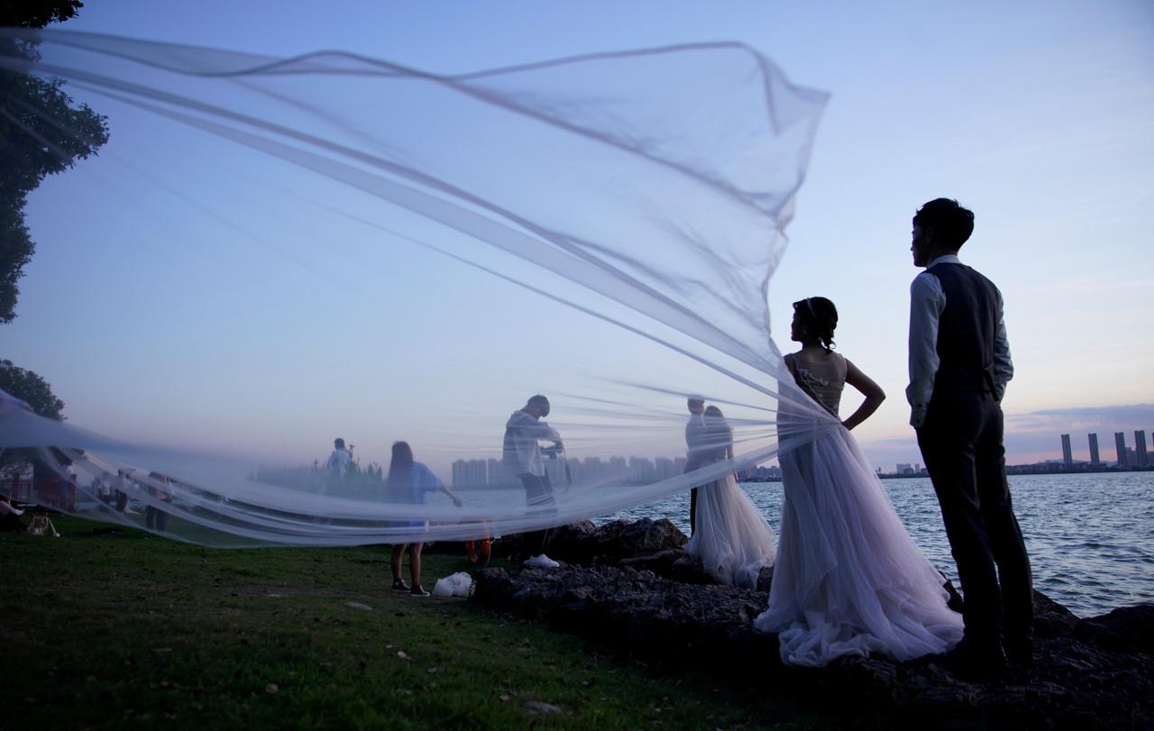 Fiatal párok pózolnak Szucsouban az esküvői fotóikhoz.
