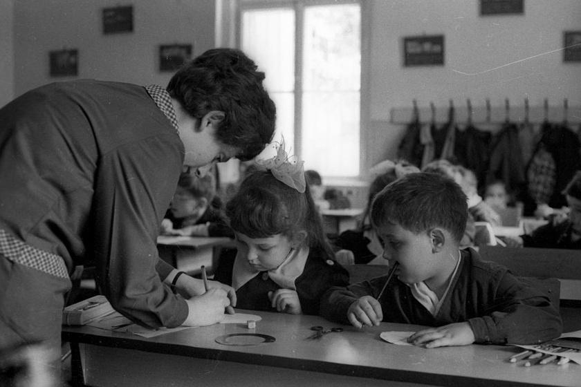 A köpenyviselés a II. világháború előtti időkből származott, a a gazdasági egyenlőtlenségek kiküszöbölésére, hogy azok a szegény gyerekek se érezzék magukat rosszul, akiknek nem jut drága holmikra. Az iskolaköpeny 1973-tól kötelező volt, ám többféle fazon is létezett. A kislányok blúzgallérját például szépen rá lehetett igazítani az elöl gombolós változatra. A fotó 1972-ben, egy rajzórán készült.