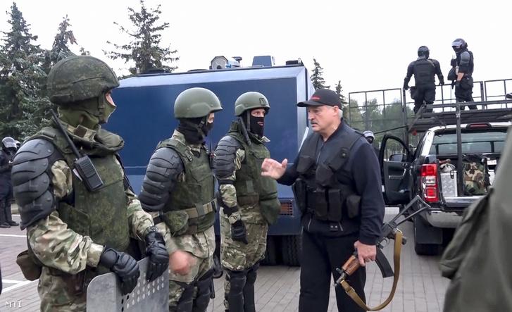 A fehérorosz állami televízió és rádió által közreadott videofelvételről készített képen Aljakszandr Lukasenka fehérorosz elnök golyóálló mellényben Kalasnyikov-géppisztollyal felfegyverkezve köszönti a minszki elnöki palotát védő rohamrendőröket 2020. augusztus 23-án