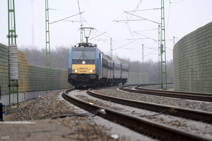 Személyvonat a hangfogó kerítésekkel védett vasúti pályaszakaszon Szolnokon