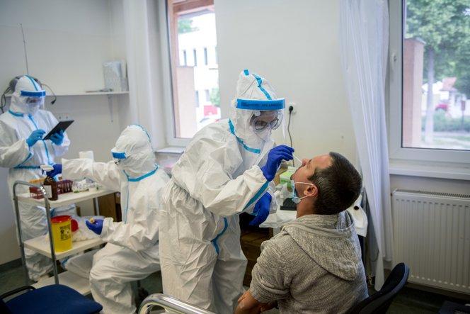 Mintát vesznek egy férfi orrnyálkahártyájáról a koronavírus-szűrések elvégzésére kijelölt rendelőben