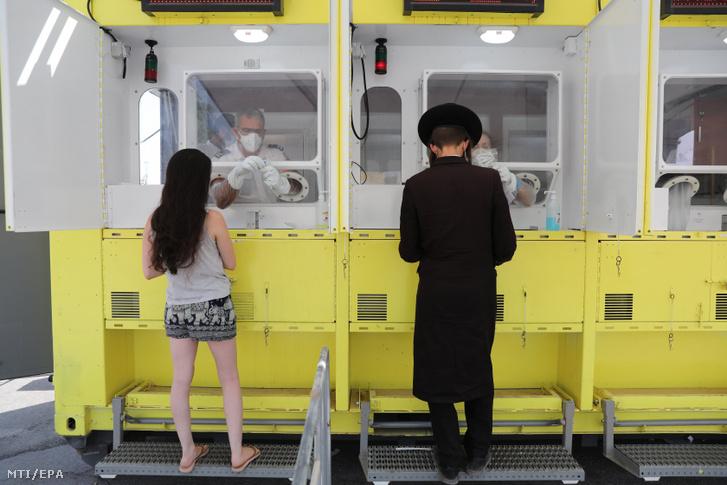 Vizsgálati mintavételre várakozó ultraortodox zsidó férfi és egy nő egy mobil koronavírus-tesztállomáson Jeruzsálemben 2020. szeptember 6-án