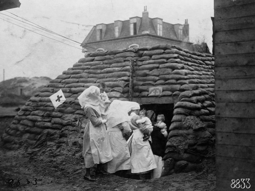 Az ápolói munka nem áll meg a kórházi keretek közti gyógyításnál. A képen a Vöröskereszt ápolói gyerekeket mentenek a homokzsákokkal megpakolt menedékhelyre az első világháborúban, 1918 novemberében.