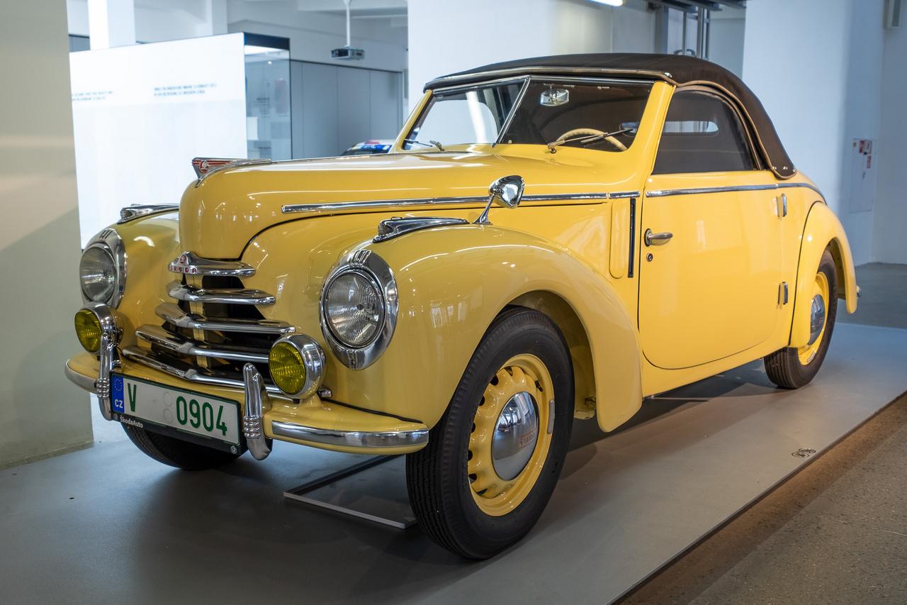 KÉP: Skoda 1100 a Skoda Museumban. Ahogy akkoriban oly sok mást, az autókereskedelmet is alapjaiban változtatta meg a Rákosi-korszak. 1951 májusától kizárólag az Autókereskedelmi Vállalaton, 1954-től az Autó és Alkatrészkereskedelmi Vállalaton keresztül lehetett új és használt gépjárművet értékesíteni. Évente néhány száz példányról volt szó, többek közt Tatraplanokról, Škoda 1101-esekről, de a felsőbb vezetésnek különlegesebb járművek is jutottak – a kapitalizmust folyton ekéző vezetők gyakran amerikai kocsikkal jártak. A képen is látható Škoda 1101-es népszerűbb neve Tudor volt, ami az angol two-door, vagyis kétajtós kifejezésből eredt. Kissé furcsa tehát, hogy később négy ajtóval is gyártották. A fotón szereplő kabrió kivitel ritkaságnak számított. A Tudorokat 1,1 literes, négyhengeres motor hajtotta, 32 lóerővel. Micsoda fejlődés az első Benzekhez képest!És mekkora a különbség egy korabeli autó és egy mai között! Az alternatív hajtások és okos megoldások új korszakot hoznak el épp napjainkban. Ezek nem csak kényelmesebbé teszik az autózást, hanem egészségügyi szempontból is nagy előrelépést jelentenek felhasználónak és környezetének egyaránt. Érdekes, hogy hasonló fejlődésen ment keresztül több iparág, köztük például a dohányipar is.
