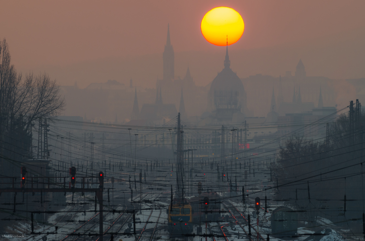 KÉP: Szmogos téli naplemente a pályaudvar felett. Az autóállomány számának növekedése folyamatos, és ezzel párhuzamosan egyre zsúfoltabbá, forgalmasabbá válnak a nagyvárosok útjai. Sok helyen épp ezért már korlátozásokon dolgoznak, sőt akár be is vezették azokat. Budapesten egyelőre csak szmogriadó esetén kell ilyesmivel számolni, azonban ilyenkor az Euro 3-asnál rosszabb benzines és az Euro 5-nél alacsonyabb besorolású dízelmotoros kocsikat kell letenni. Természetesen nemcsak a városok vezetői gondolkodnak korlátozásokban. Az autógyártóknak is egyre szigorodó normáknak kell megfelelniük, évről évre alacsonyabb károsanyag-kibocsátású modellekkel állnak elő. A legtöbben a hibridekben vagy a teljesen elektromos megoldásokban látják a jövőt. Ennek megfelelően nemcsak a prémiumgyártók kínálatában találunk ilyen típusokat, vagyis az ártalomcsökkentett megoldások egyre szélesebb körben érhetők el.