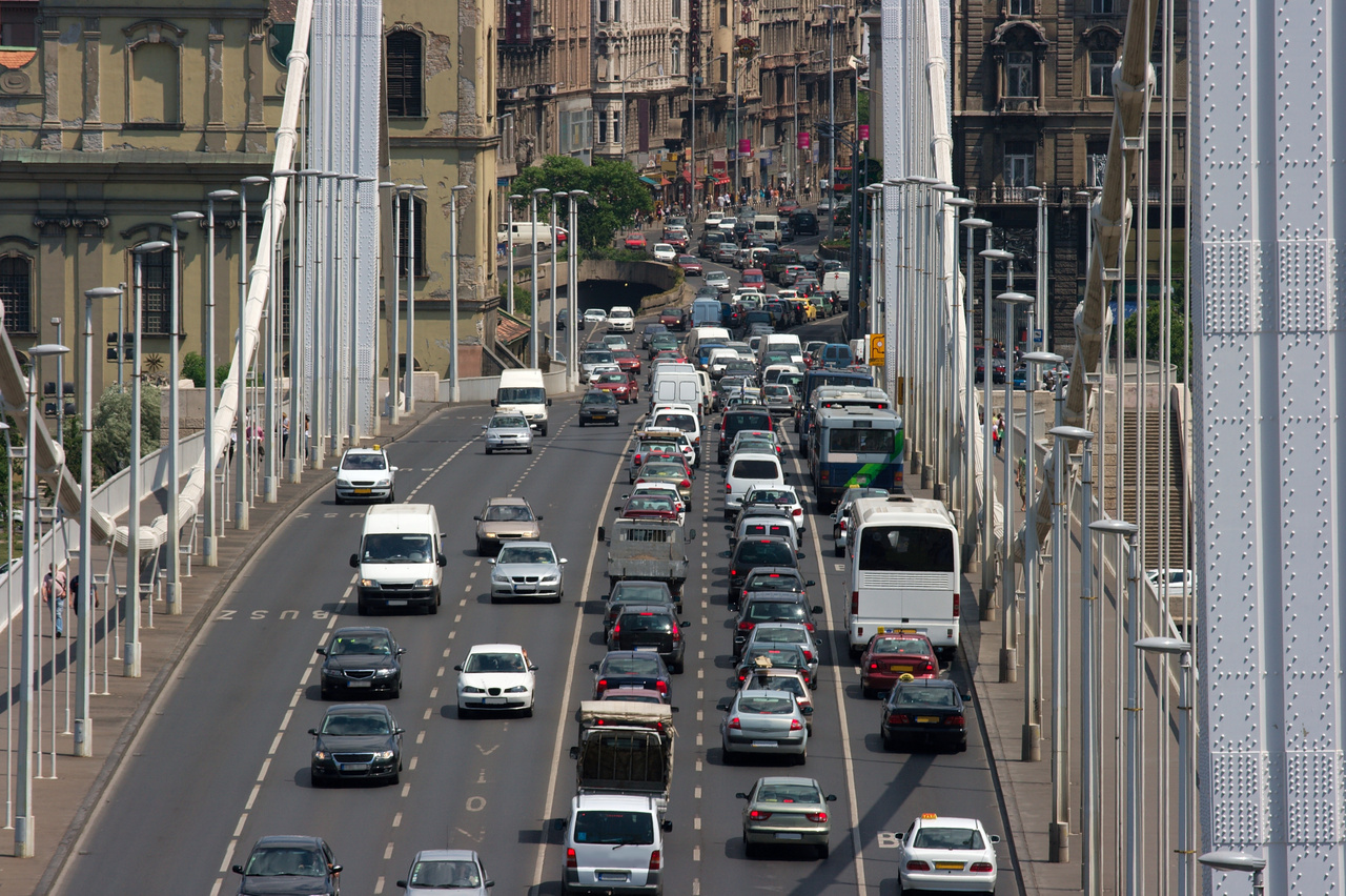 """KÉP: Szokásos forgalom az Erzsébet hídon.Az ezredfordulóra mintegy 2,36 millió autó volt forgalomban Magyarországon. A növekedés innentől kezdve egészen 2008-ig folyamatos volt, akkor azonban jött a válság, ami visszaesést hozott mind az újautó-eladásban, mind pedig a hazai gépjárműállomány számában. Csak 2012-ben indult újra az emelkedő tendencia, és 2019 végén már 3,8 millió személyautó volt forgalomban. A márkák közül az Opel a leggyakoribb, de dobogós a Suzuki és a Volkswagen is.Ahogy az autós közlekedés korszerűsítése, a tömegközlekedésben bevezetett szabályozások, újítások és ezeken túl még a légszennyezés kérdése is a társadalom egészét érintő témák, úgy például a dohányzás is,  hiszen hazánkban több mint kétmillió ember dohányzik, de közvetve szinte mindenkit érint.  Azoknak az autósoknak, akik környezettudatosabban szeretnének közlekedni, a hibrid autótól az elektromosig, többféle """"füstmentes"""" alternatíva áll rendelkezésükre, akárcsak a dohányosoknak. A technológiai fejlődés ugyanis a dohányzás területén is  tetten érhető.Azon felnőtt dohányosok, akik valamilyen okból nem teszik le a cigarettát, ma már számos füstmentes alternatíva közül választhatnak. Ilyen például a nikotinsóval működő technológia, a nikotintartalmú folyadék elektronikus hevítésén alapuló e-cigaretta, vagy a dohány-hevítéses technológia. Ezekben közös, hogy égés és füst nélkül működnek, de az adott technológiákon belül óriási különbségek vannak, emiatt fontos a megbízható forrásból történő tájékozódás, akárcsak az autóvásárlás előtt. Persze ezek a technológiák sem kockázatmentesek, hiszen például tartalmaznak nikotint, és az elektromos autók sem 100%-ban ártalmatlanok a környezetre."""