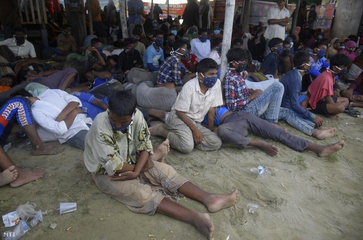 Rohingja nemzetiségű muzulmánok pihennek, miután hajójukkal megérkeztek az indonéziai Aceh tartomány Lhokseumawe településének tengerpartjára 2020. szeptember 7-én. Csaknem 300 rohingja nemzetiségű muzulmán menekült szállt partra a csónakból.
