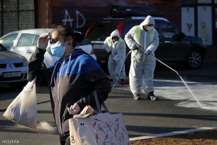 A koronavírus-járvány elleni védekezésképpen fertőtlenítenek egy bukaresti utcát védőruhás városi alkalmazottak 2020. április 6-án.