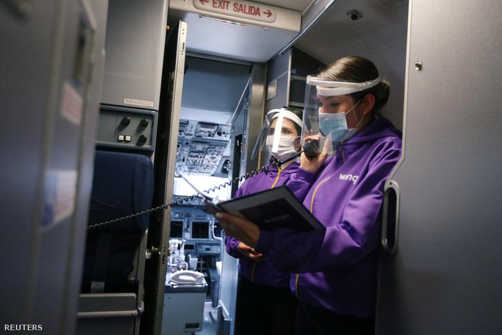Egy légitársaság alkalmazottai arcmaszkban és pajzsban a repülőgép belsejében 2020. augusztus 31-én