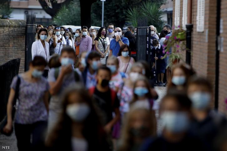 Védőmaszkos szülők és hozzátartozók nézik a római San Policarpo-plébániára bemenő tanulókat az első tanítási napon, 2020. szeptember 14-én