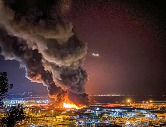 Sűrű füst száll fel az olaszországi Ancona kikötőjéből 2020. szeptember 16-án. A tűzoltók arra számítanak, hogy estére tudják teljesen eloltani a tüzet. A tűz keletkezésének oka még nem ismert.