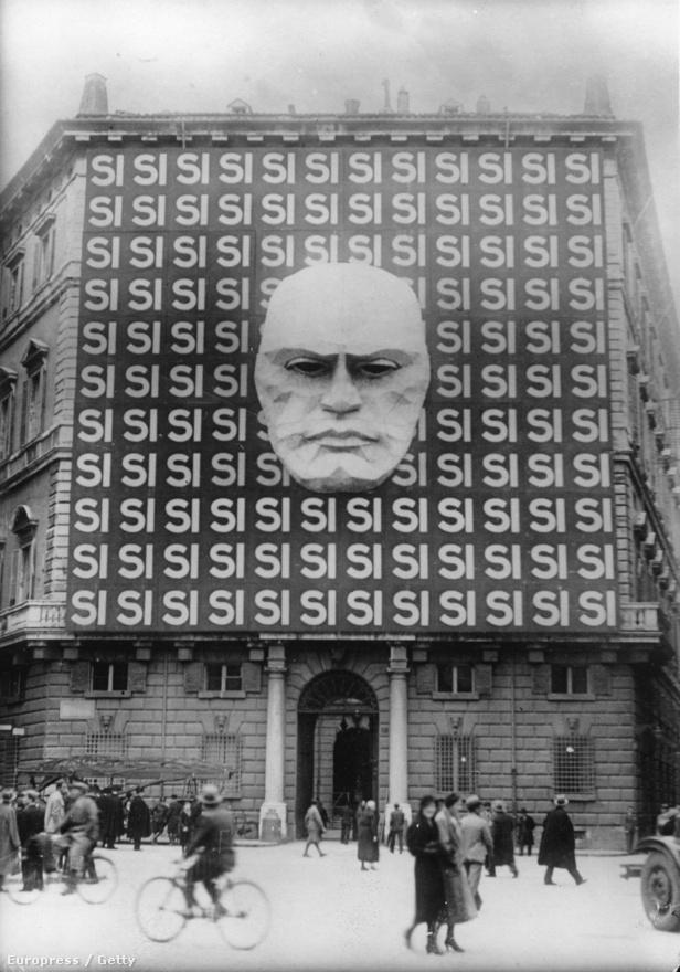 Propagandaplakát 1934-ben a Palazzo Braschin. A neoklasszikus épületet a fasizmus alatt Mussoliniék főhadiszállásként használták. A háború után 300 menekült család lakott benne, akik a hideg miatt tüzeket raktak az épületben. Ekkor égett le a falakról a freskók nagy része.