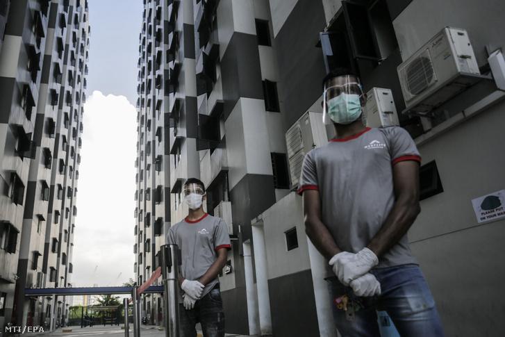 Arcvédő pajzsot és szájmaszkot viselő férfiak a Westlite Papan nevű külföldi munkavállalók számára létesített szálló épülete előtt Szingapúrban 2020. május 15-én.