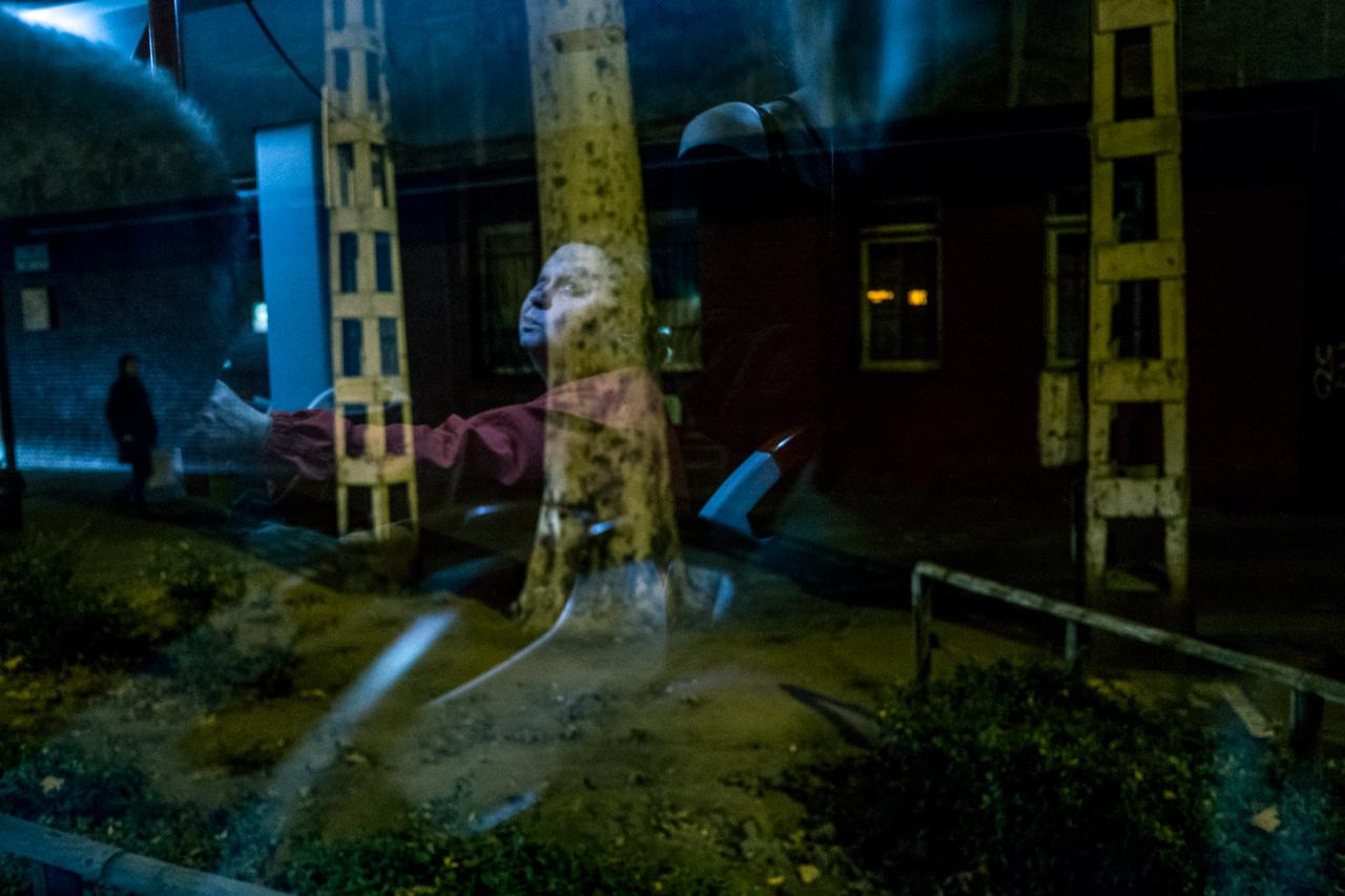 Festményszerű kép a troliról fotózva. A nem klasszikusan szép alany a fényeknek hála kiragyog a sivár éjszakából.