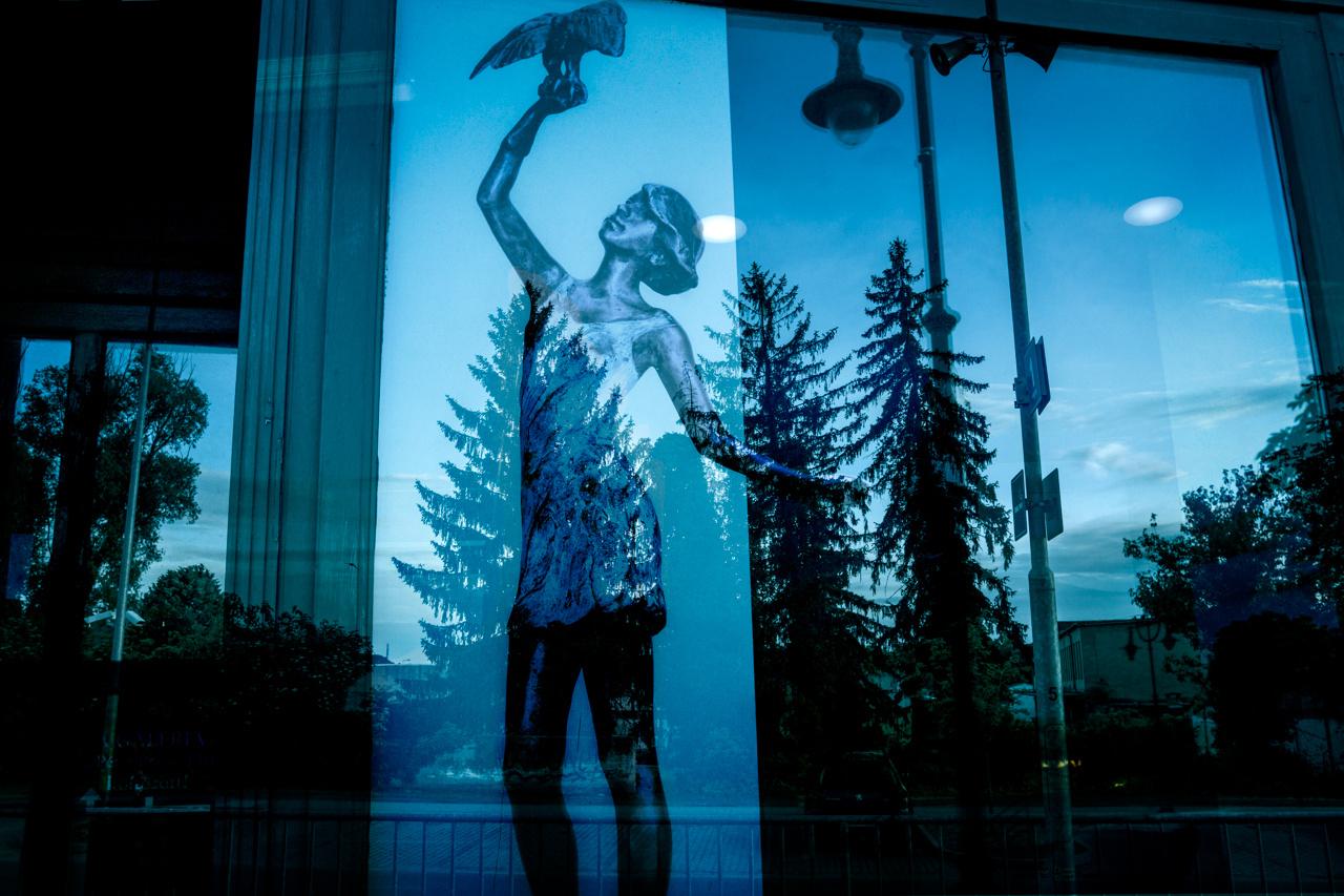 A plakátlány és a vonat ablakából készített tájkép hangulatosan mosódik össze.