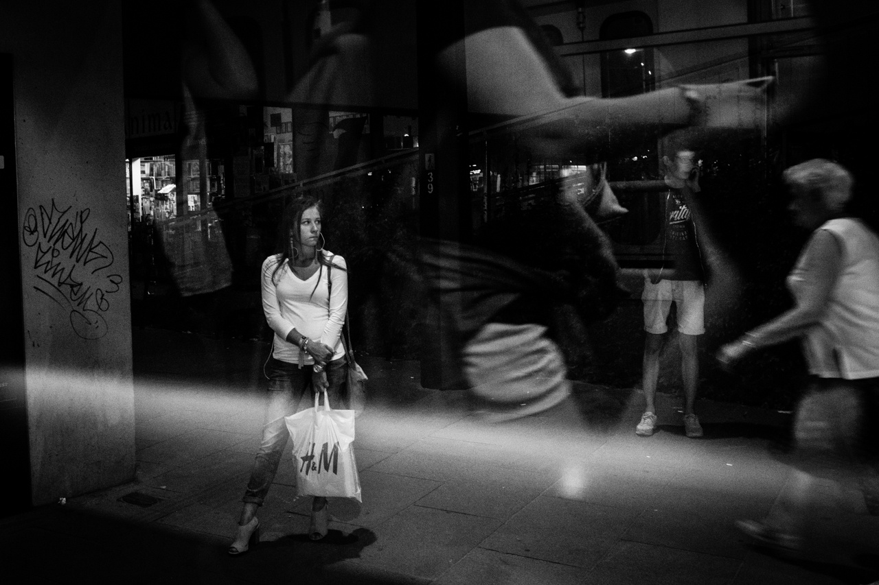 Moszkva téri éjszakai életkép, sok réteggel és részlettel. A kép a mozgó alakoktól és a lendülő karoktól válik dinamikussá.