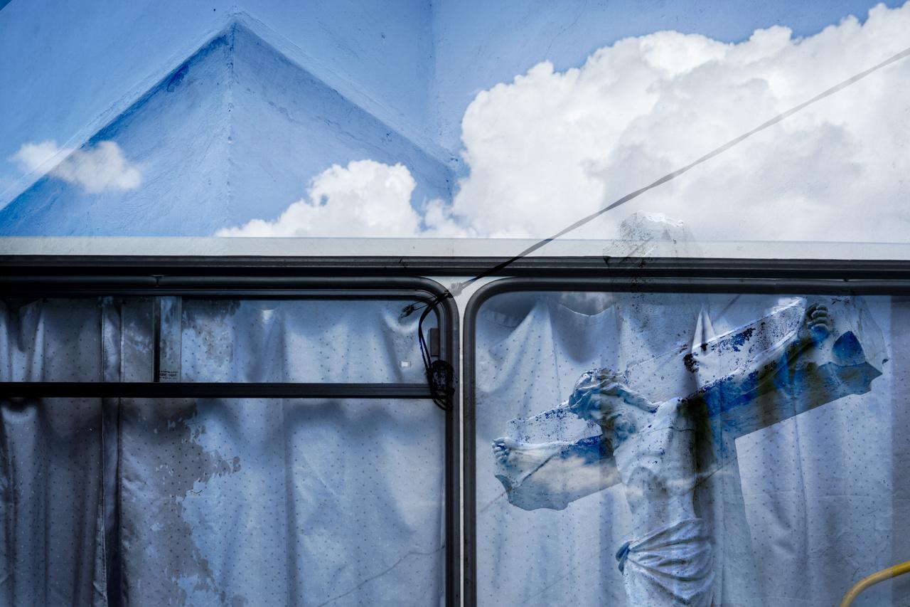 Multiexpo eljárással készült fotó, azaz itt két kép található egymáson. A szürrealitás tárgya a régi Ikarus ablakában tükröződő Jézus Krisztus. A fotót a felhők miatt is valami  finom túlvilági hangulat lengi körül.
