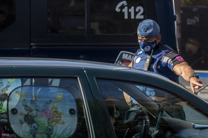 Megállít egy autót egy rendőr egy ellenőrző pontnál Madrid Usera kerületében 2020. szeptember 22-én, miután az előző nap a koronavírus-járvány miatt kijárási korlátozást vezettek be a negyedben