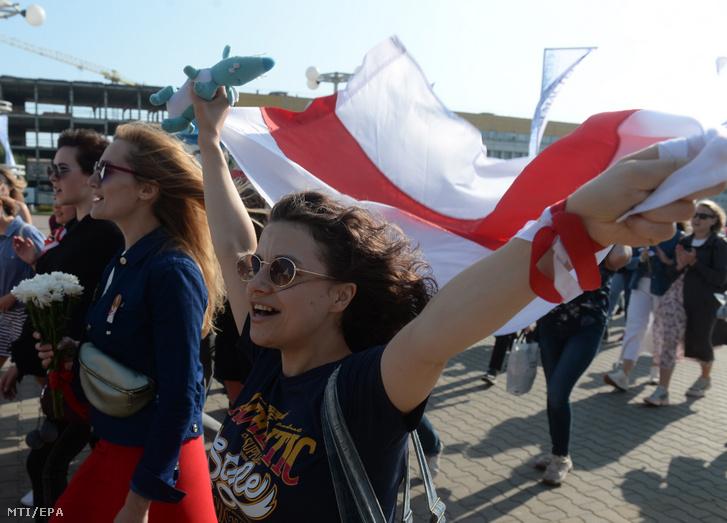 Virágcsokrokat és zászlókat tartó nők egy békés szolidaritási felvonuláson Minszkben 2020. szeptember 26-án