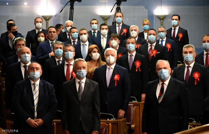 A koronavírus-járvány miatt védõmaszkot viselõ képviselõk állnak a padok között az új montenegrói parlament alakuló ülésén Podgoricában 2020. szeptember 23-án.