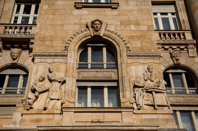 Két pártra osztott szobrok a jegybank épületének homlokzatán.