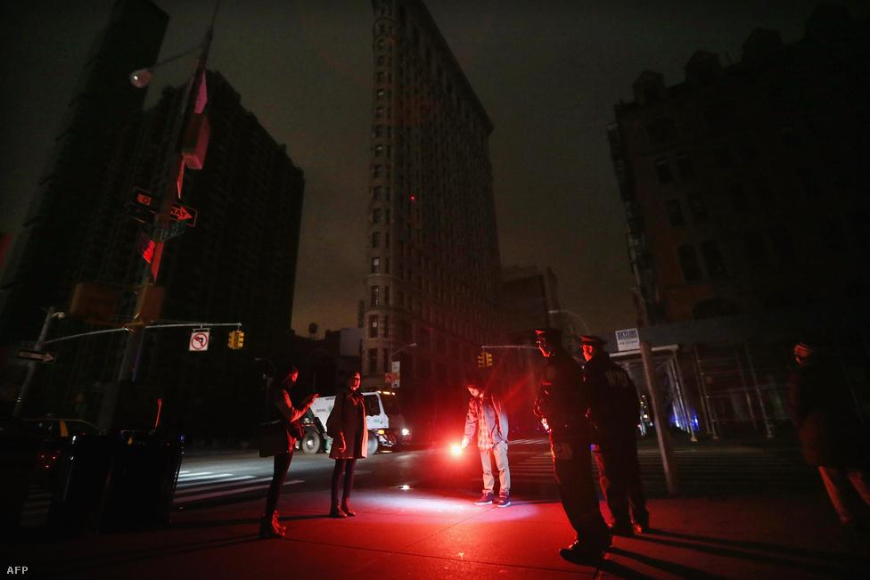 Rendőrök szólítanak fel egy férfit Manhattan híres vasalóház előtt, hogy oltsa el fáklyaként használt jelzőrakétáját.