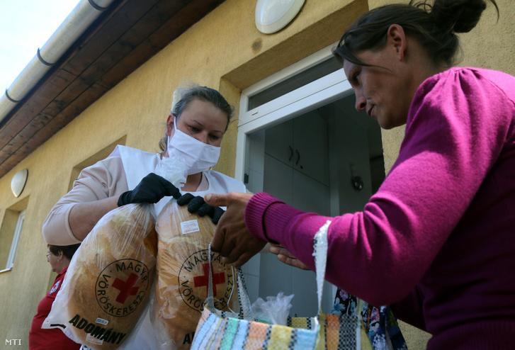 Egy asszony átveszi az élelmiszer-adományt egy önkéntes munkatárstól Hernádvécsén 2020. május 22-én. A Magyar Vöröskereszt 36 nehéz sorsú családnak tejet és kenyeret ad a megyében heti rendszerességgel az Auchan az Ifjúságért Alapítvány pályázatának támogatásával a Gyermekszáj program keretében.