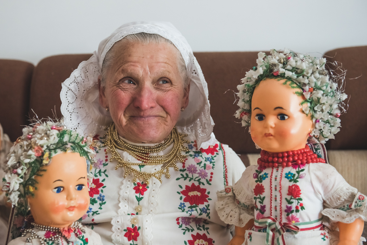 Kétbodonyi palóc viselet. A babák is ebben pompáznak. A huncut mosoly a 80 éves Anka néni arcáról letörölhetetlen.