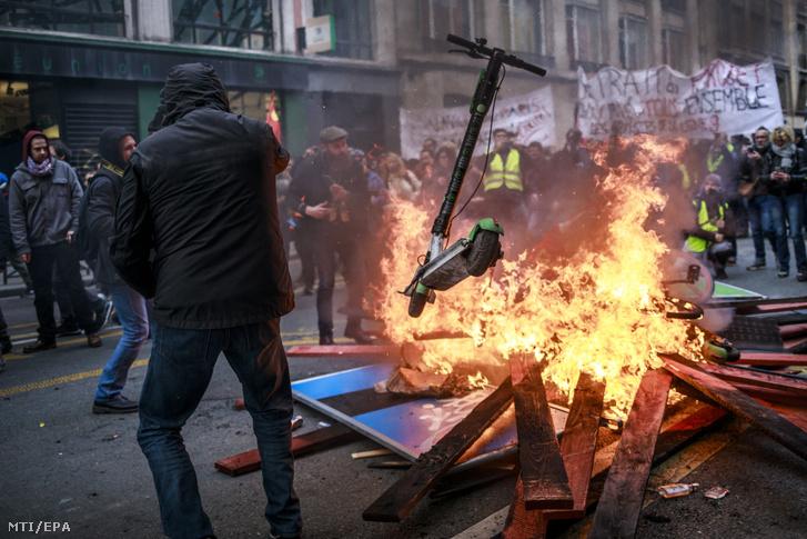 Az egyik tüntető scootert hajít a tűzbe egy felgyújtott útakadálynál Párizsban a kormány tervezett nyugdíjreformját ellenző általános sztrájk huszonnegyedik napján, 2019. december 28-án. A szakszervezetek december 4-én határozatlan idejű munkabeszüntetést hirdettek a jelenlegi 42-féle nyugdíjrendszer egységesítésére irányuló, pontrendszer alapú reformtervezet ellen.