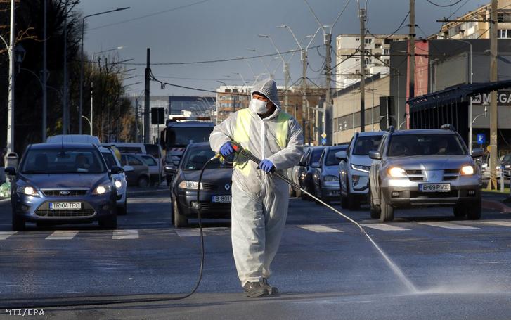 A koronavírus-járvány elleni védekezésképpen fertőtlenít egy bukaresti utcát védőruhás városi alkalmazott 2020. április 6-án.