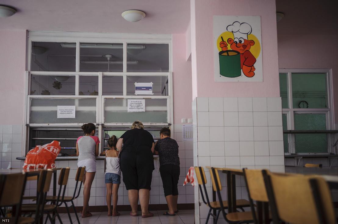 Elvitelre kapott ebédért állnak sorban rászorulók a debreceni Lilla Téri Általános Iskola Nagysándor József Általános Iskolai tagintézményének konyháján