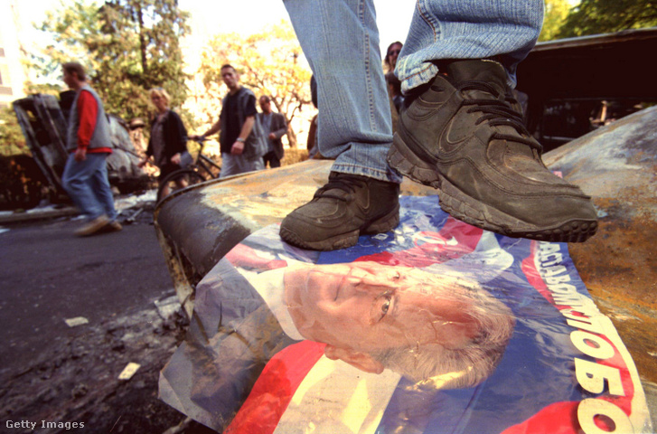 Egy ellenzéki tüntető 2000. október 6-án Slobodan Milošević plakátján táncol a jugoszláv szövetségi épület mellett Belgrádban