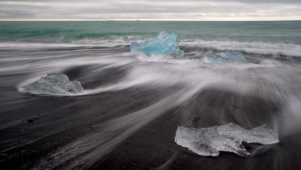 Jeges óceánpart                         1.díj (Tájak)                         Izlandi utunk során egy éjszakát töltöttünk Jökursárlón gleccsertava mellett, ami végül az egyik legfagyosabb esténk volt a szigeten – de megérte! A tavat a Brei∂amerkurjökull-gleccser táplálja, és az arról leváló jégtömböket az áramlatok sodorják ki az óceán partjára. A gleccser folyamatosan zsugorodik, régebben lényegében elérte az óceánt, míg napjainkban a vége már csaknem két kilométerre van a parttól. A környék Izland egyik fő látványossága, a tó, a jeges part és a számtalan árnyalatban pompázó jég sokszor szürreális élményt nyújt.