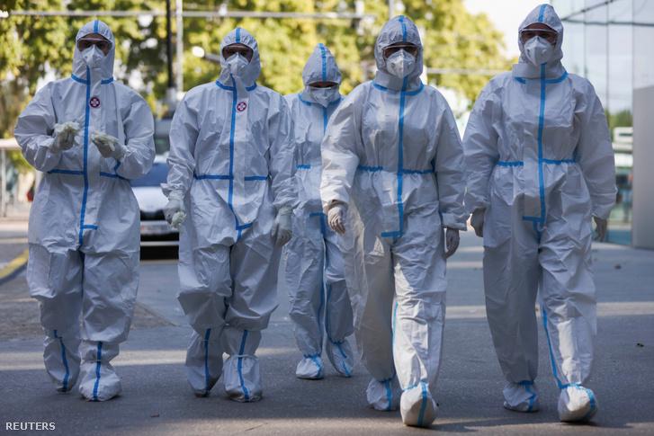 Egészségügyi dolgozók érkeznek védőöltözetben egy bécsi koronavírus-tesztelő állomásra 2020. szeptember 23-án