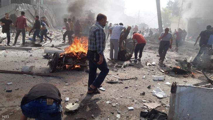 A Fehér Sisakosok nevű szíriai polgári védelmi szervezet által közreadott kép civilekről a pokolgépes merénylet helyszínén, a Törökország által támogatott felkelők ellenőrzése alatt álló észak-szíriai Al-Bab városában 2020. október 6-án. Az autóba rejtett pokolgéppel elkövetett támadásban legkevesebb tizennégyen életüket vesztették