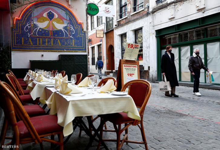 Üres étterem terasza előtt sétálnak Brüsszelben 2020. október 16-án