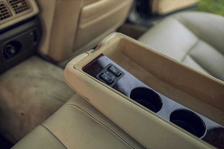 Hátul a lehajtható könyöklő fabetétet, pohártartót és a hátsó ülések fűtésének kapcsolóit rejti.