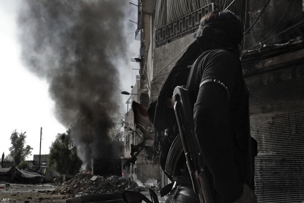 Felkelő figyel egy égő buszt Aleppóban, ahol szemtanúk szerint napok óta szünet nélkül hallani a nehéztüzérség és a légierő bombáinak robaját.