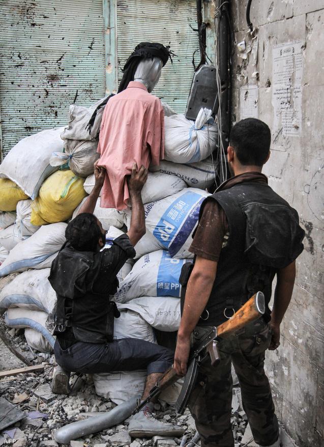 Beöltöztetett csalit helyeznek el felkelők egy lőrésnél Aleppóban. Az utcai hadviselésnek is fontos eleme a megtévesztés.