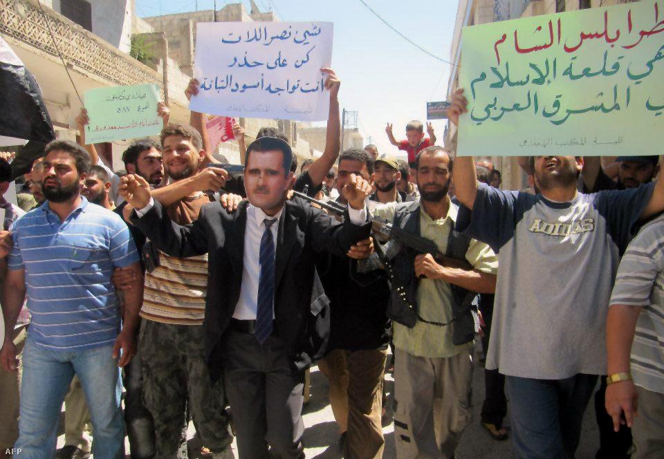 Aszad elnök képmását viselő férfi demonstrál a felkelőkkel Homszban. A felkelők hírügynökségének felvétele.