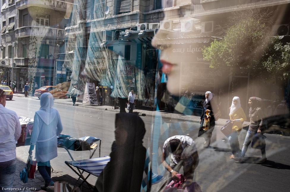 Utcakép egy damaszkuszi ruhaüzlet kirakatának üvegén át. Sok kereskedő menekült a fővárosba a felkelés elől, Damaszkuszban viszont a vevőkért kell harcot vívniuk az elszegényedett városban.