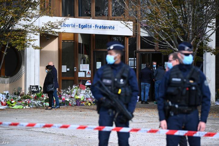 Emberek virágot visznek a gyilkosság helyszínére Conflans-Sainte-Honorine-ban 2020. október 19-én