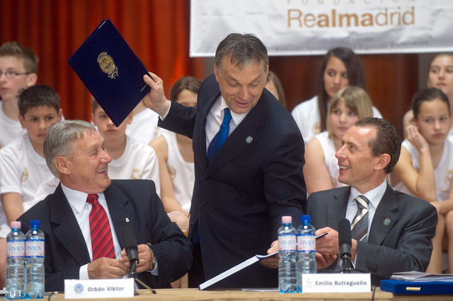 Orbán Viktor miniszterelnök a felcsúti Puskás Ferenc Labdarúgó Akadémia alapítója (k) kicseréli a dokumentumokat amelyeket Kovács Ferenc a Puskás Akadémia Szakmai és Irányító Testületének tagja (b) Emilio Butragueno a Real Madrid CF intézményi kapcsolatokért felelős igazgatója (j) írt alá a felcsúti RealTanoda megalakulásáról melynek értelmében a 2011-12-es tanévtől három éven át szociális sportiskola indul Felcsúton.
